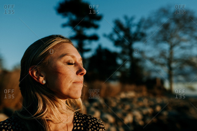 peaceful woman with eyes closed on the beach at sunset
