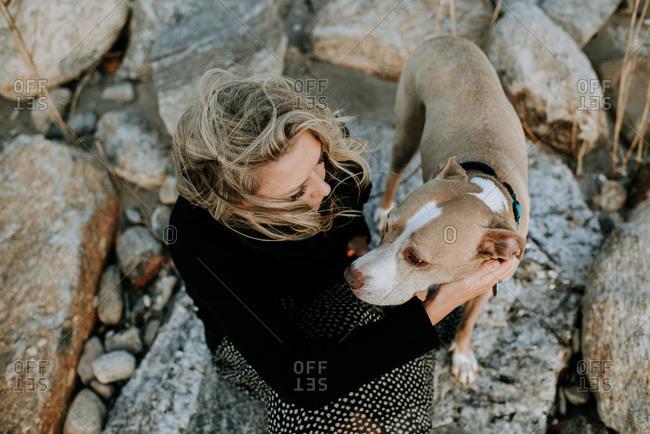 woman and dog sitting on rocks