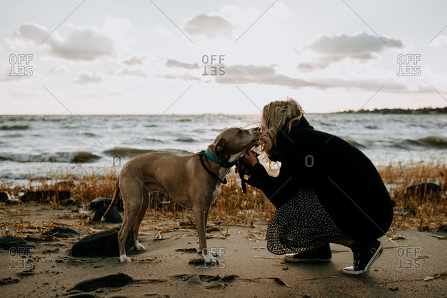 woman kissing her dog on the beach in the wintertime