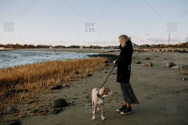 woman standing on beach with dog in wintertime
