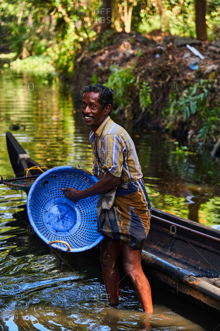 Alleppey, Kerala, India - February 18, 2019: Man standing in river with basket by boat collecting water chestnuts