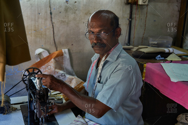 Alleppey, Kerala, India - February 18, 2019: Indian man sewing on an old sewing machine