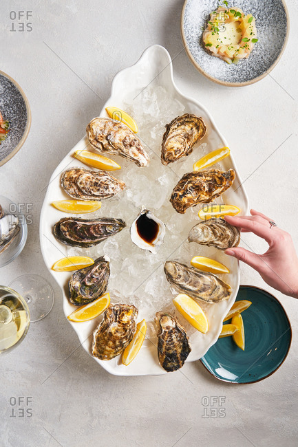 Hand reaching for oyster from platter