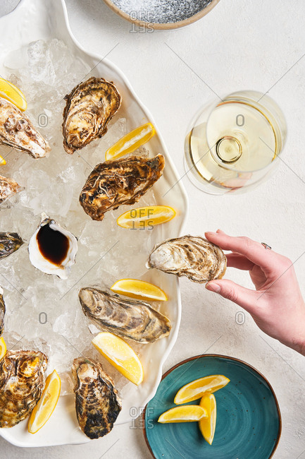 Hand reaching for oyster from platter with lemon and ice