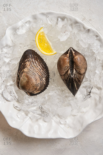Close up of a clam appetizer and lemon in a dish with ice