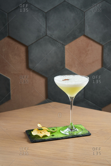 Foamy cocktail on slate board with dried apples