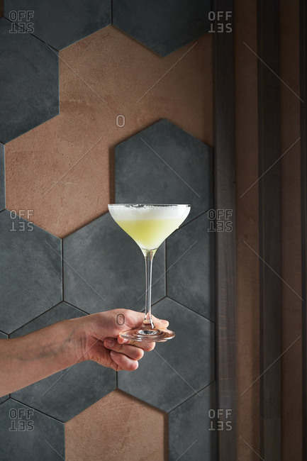 Hand holding a foamy cocktail in front of a background with hexagon tiles