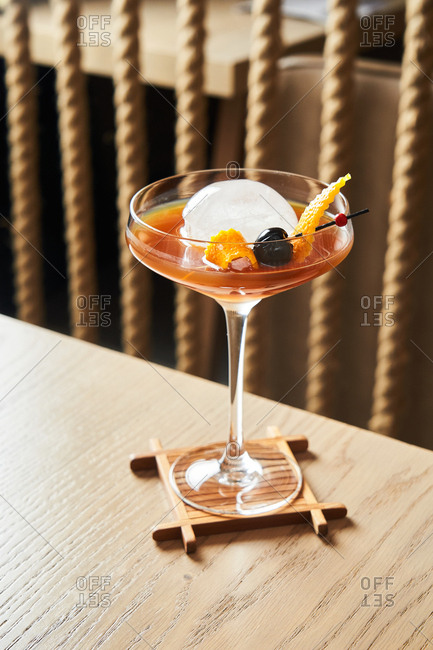 Old fashioned cocktail with round ice in a coupe glass