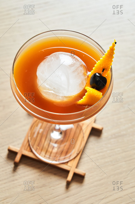 Overhead view of an old fashioned cocktail with round ice in a coupe glass