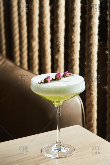 Green foamy cocktail with flower garnish
