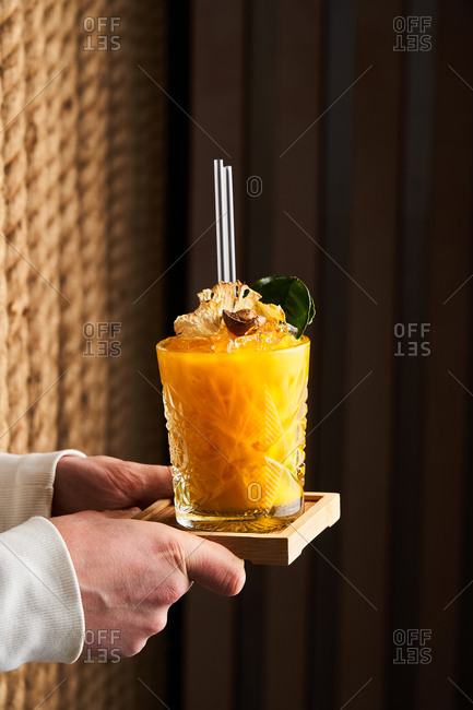Hand holding a tropical cocktail on a wooden coaster