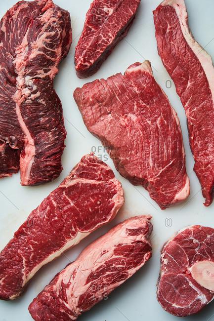 Raw steaks on light background