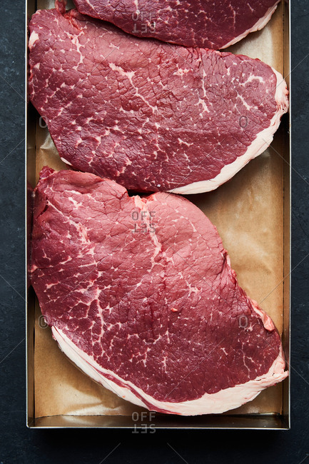 Pan filled with large raw steaks