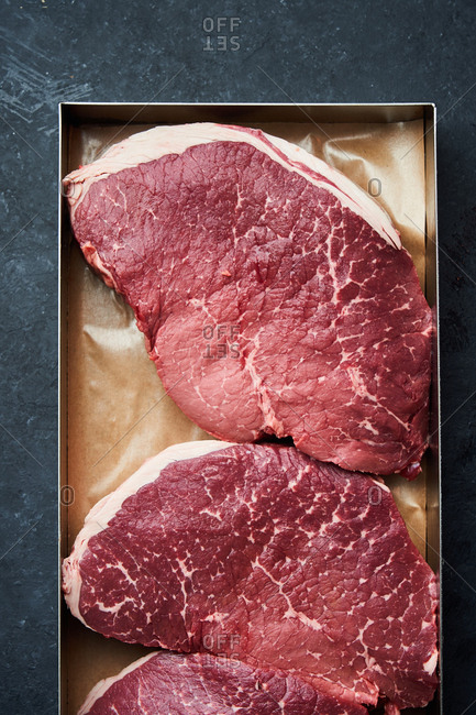 Overhead view of a pan filled with large raw steaks