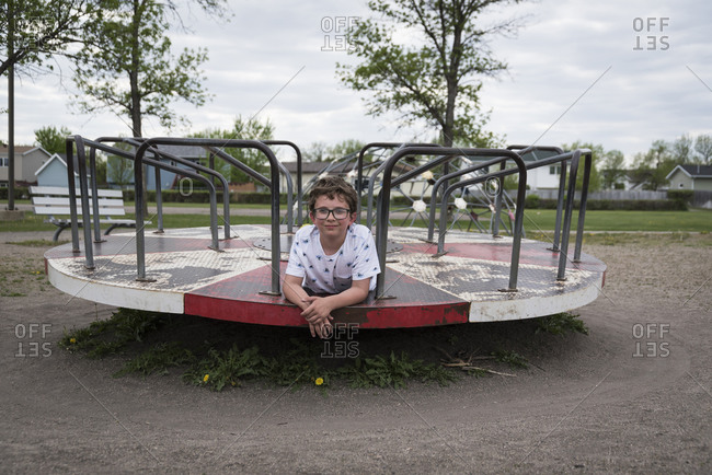 Portrait of boy lying on merry-go-round at playground