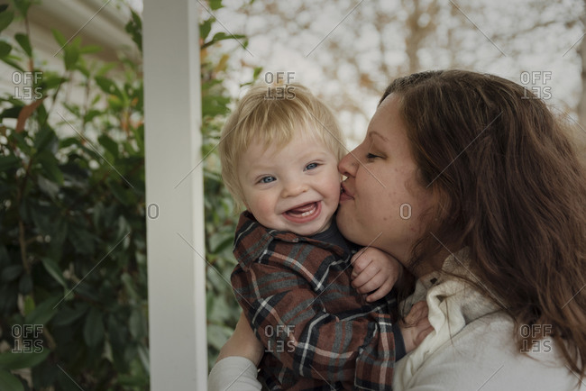 Close-up of mother kissing happy son's cheek in porch