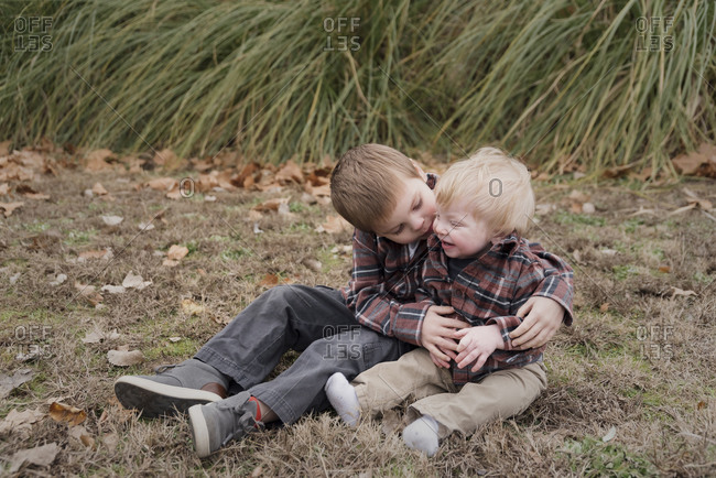 Boy kissing cute brother while sitting on field at park