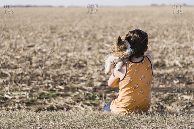 Boy holding puppy on the side of a dirt road in the country.