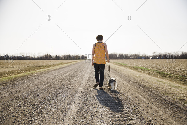 Boy and dog walking on a road in the country with a clear sky.