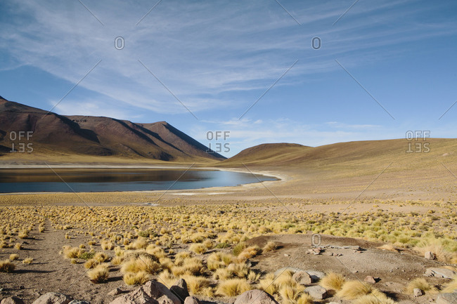 Scenic view of lake by mountains at desert against sky