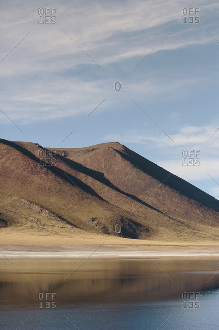 Tranquil view of lake by mountains at desert against sky