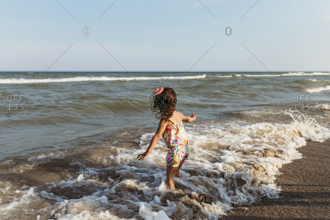 Carefree girl playing in waves at beach against clear sky