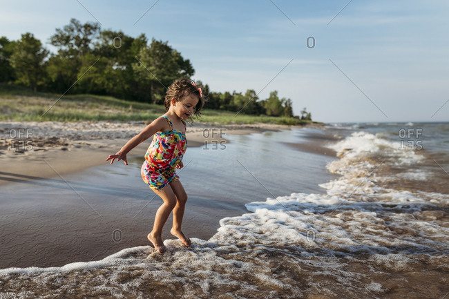 Playful girl jumping in waves at beach against sky