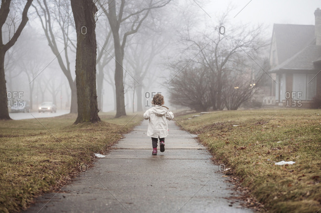Rear view of girl wearing raincoat while walking on footpath during foggy weather