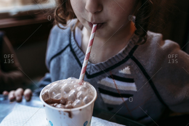 Midsection of playful girl blowing bubbles in chocolate milk at home