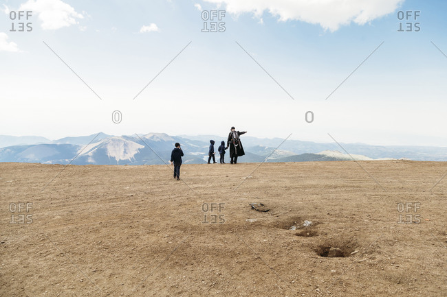 Rear view of father and children standing on mountain against sky