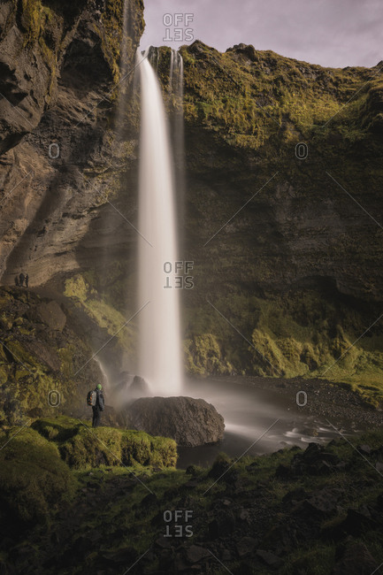 Man observing the size of a waterfall