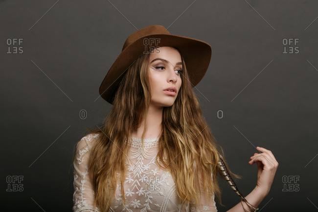 Fashion portrait of young beautiful woman wearing hat and white blouse