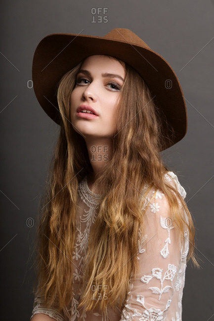 Portrait of young long haired woman wearing hat