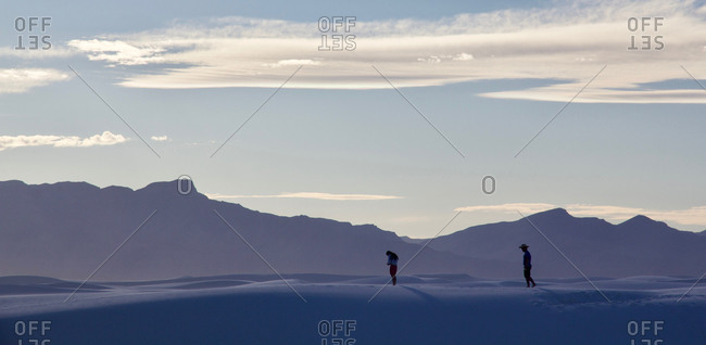 Two silhouettes standing on a sand dune