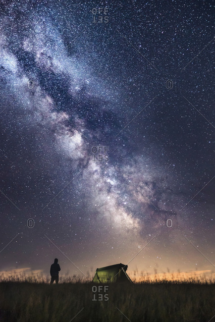 Silhouette of climber standing next to the tent watching the stars