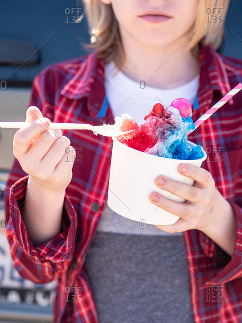 Young person getting spoonful of colorful shaved ice