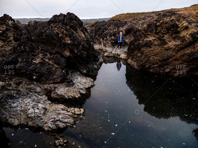 Tween boy standing on the edge of pool of water on the coast
