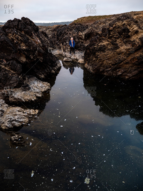 Young boy standing by large tide pool on the coast of California