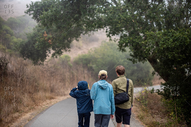 3 young men hiking on foggy trail