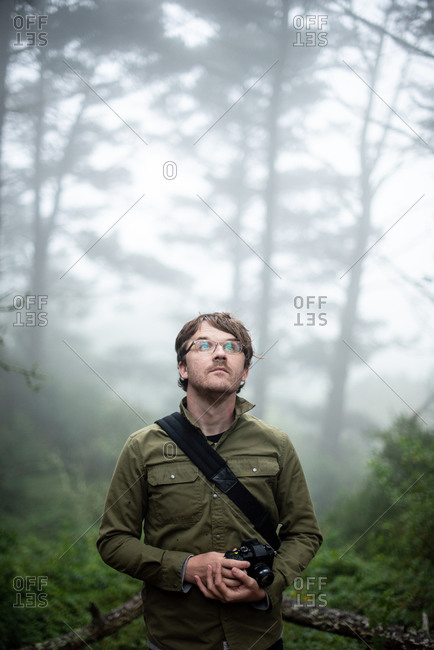Portrait of photographer looking up into trees holding camera