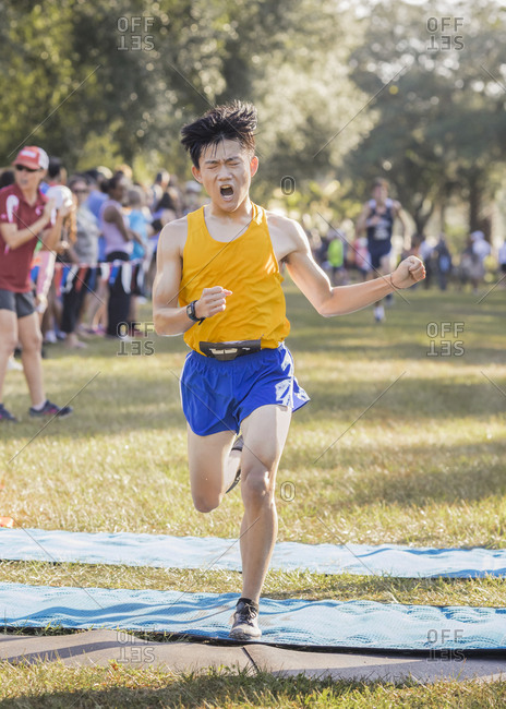 Asian high school cross country runner crosses finish line emotional