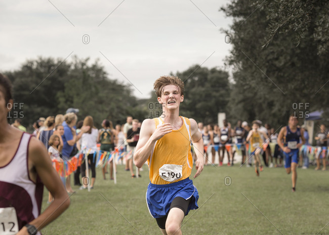 Teen male cross country runner with braces crosses finish line in race