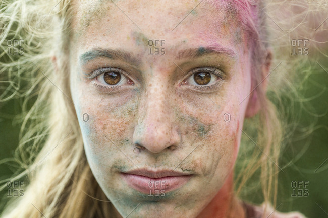 Caucasian teen girl covered in colored powder after color run