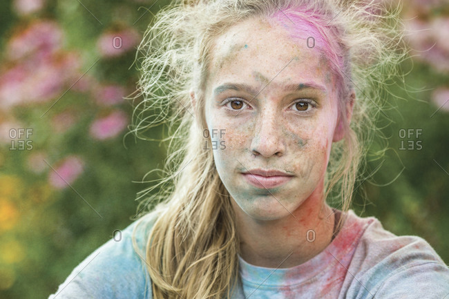 Caucasian girl covered in colored powder after color run