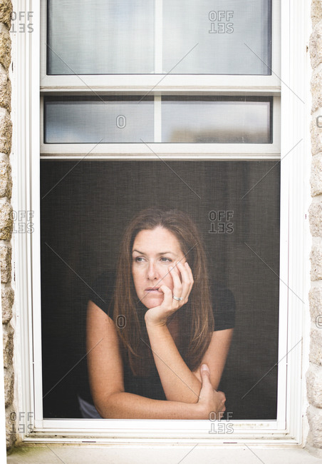 Tired woman looking out of open window with chin resting on hand.