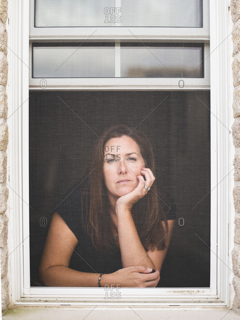 Woman looking out of open window with chin resting on hand.