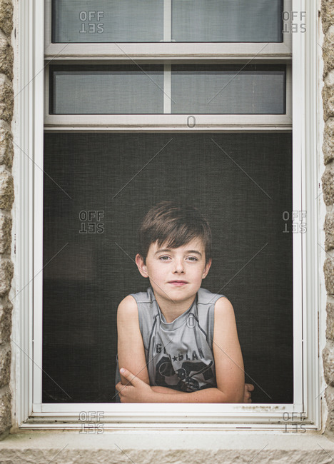 Young boy looking out through the screen of an open window.