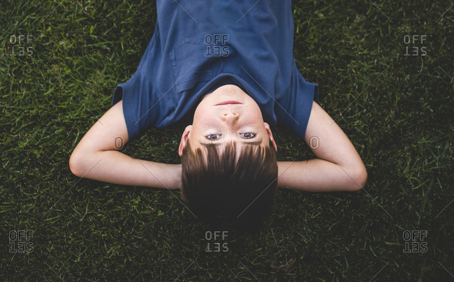 Upside down image of boy laying on grass with arms behind head.