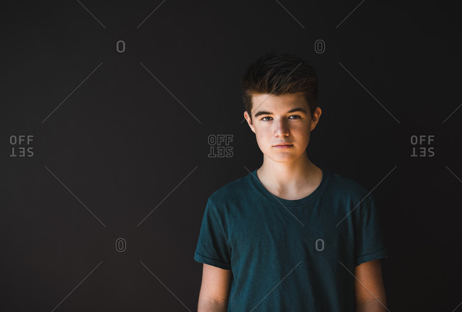 Portrait of a caucasian teenage boy against a dark background.
