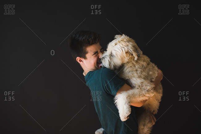 Teenage boy holding a fluffy dog that his licking him on the face.